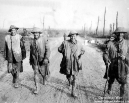 Four Canadian Highlanders wearing kilts, respirator bags, and smiles walk along a muddy path away from the front lines.