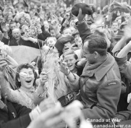 Joyous Dutch civilians celebrate the liberation of Utrecht. Dutch women hand tulips to members of the Canadian Army. May 7, 1945.