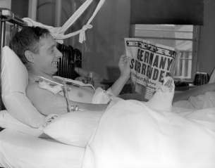 William George Lucas (1909-1997), 3rd Anti-tank, 3rd division, reads about the good news while staying at Shaughnessy Hospital in Vancouver.