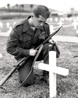 Canadian Ssoldier holding a rifle kneels before comrade's grave, a white cross