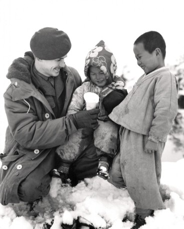 A soldiers sits with two Korean kids in the snow. He is handing a snow cone to a little girl.