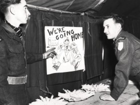 Two Canadian soldiers stand in front of a poster that says We're Going Home (End of the Korean War)