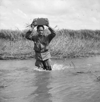 A young René Levesque carries his mini-tape recorder on his head through a stream