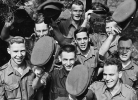 A group of Canadian soldiers take off their hats to celebrate the signing of the Korean Armistice