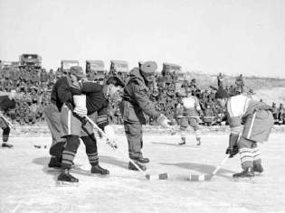 Canadian soldiers play hockey during Korean War.