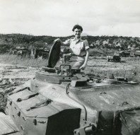 Nesta Bass, part of the Queen Alexandria's Royal Army Nursing Corps, sits on top of a tank.