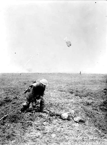 A Canadian soldier observes a fallen German soldier who is beyond human aid. (Vimy Ridge).