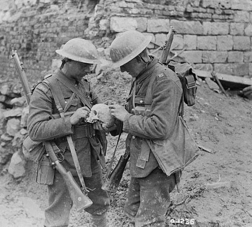 Two soldiers examine a skull found on the battlefield at Vimy Ridge